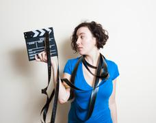 Young pretty woman with filmstrip around neck holds movie clapper Stock Photos