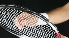 Close up of a tennis player's hand adjusting the net of his tennis racket Stock Footage