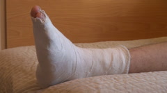 Teenage boy making exercises, broken leg, plaster cast, recovery, muscle, bed Stock Footage