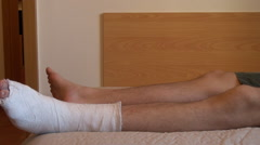 Sad young man suffering, lying on bed, leg, fracture, plaster cast, painful - stock footage