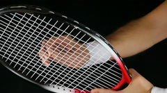 Slow motion of a tennis player's hand adjusting the net of his tennis racket Stock Footage