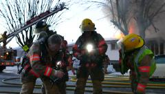 4K UHD - Fire fighters donning gear in closeup with flames in background Stock Footage