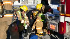 4K UHD - Group of fire fighters rescuing a dog with oxygen near a firetruck Stock Footage