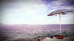 Alone beach retro style umbrella on the mediterranean croatian shore Stock Footage