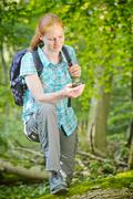 Hiker Using GPS Navigation in a Forest - stock photo