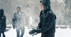 Asian man blizzard wiping snow off gloves Washington Square Park Manhattan NYC Stock Photos