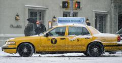 Taxi Cab Turning Corner on 5th Ave in Manhattan in blizzard snow storm - stock photo