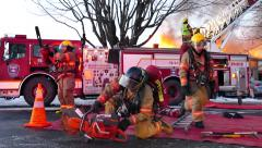 4K UHD - Fire fighters testing saws and gathering tools at inferno Stock Footage