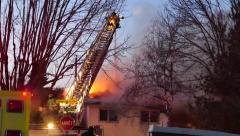 4K UHD - Fireman atop of ladder shooting water onto house fire with flames Stock Footage
