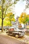 A retro car parked near a water canal Stock Photos