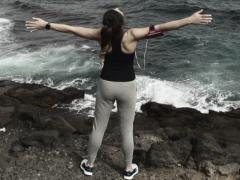 Woman enjoying view with wide open arms standing on rocks by sea NTSC Stock Footage