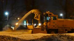 4K UHD - Snowblower at night clearing the road and shooting snow away Stock Footage