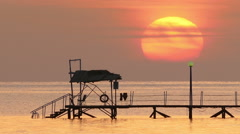 beautiful sunrise over pier in sea - filmed at telephoto lens - stock footage