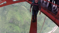 Base jumper jumps from a bridge with spectacular views of surrounding landscape Stock Footage