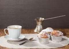 Cup of coffee with tasty muffins and turk for coffee - stock photo