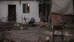 Ruined old house made of mud with old children's staff in the yard, tilt down. Stock Footage