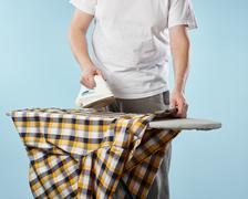 Household chores, ironing man - stock photo