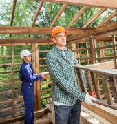 Construction Workers Working In Timber Cabin At Site - stock photo