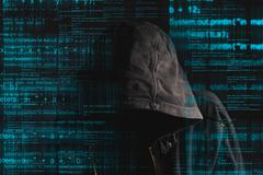 Faceless hooded anonymous computer hacker Stock Photos