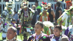 Women prance in front of pow wow dancers Stock Footage