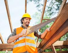 Happy Worker Cutting Wood With Handsaw At Site Stock Photos