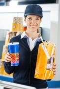 Worker Holding Popcorn And Drink At Cinema Concession Stand - stock photo