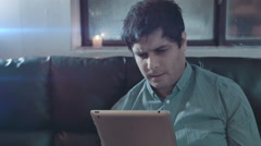 Mixed race man reacts negatively to something on his tablet. Stock Footage