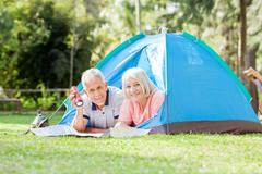 Senior Couple With Torch And Map In Tent Stock Photos