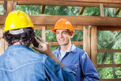Happy Architect Looking At Colleague Using Cellphone - stock photo