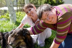 Two women and a half breed dog Stock Photos