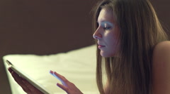 Young girl lying on bed and using tablet computer for online shopping - stock footage