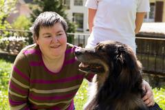 disabled woman is caress a dog - stock photo