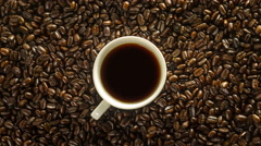 Cup of coffee rotation on the background of roasted coffee beans 4K Stock Footage