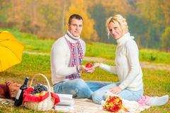 Man and woman hold in their hands a red apple Stock Photos