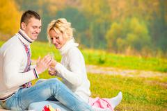 heterosexual couple relaxing cheerfully in the park - stock photo