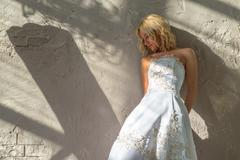 Bride stands about the plastered walls - stock photo