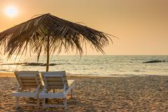 beautiful empty beach and a pair of sun loungers - stock photo