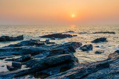Bright orange sun over the sea and rocky shore Stock Photos