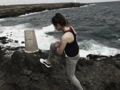 Young woman stretching leg on rocks by sea, slow motion shot at 240fps  NTSC Stock Footage