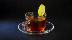 Cup of tea with lemon rotation on the black background 4K Stock Footage