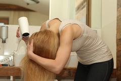 Blow-drying hair - stock photo