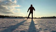 Cross-country skiing on a flat surface of a pond on a warm day - stock footage