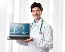 Handsome Doctor showing laptop with heartbeat Stock Photos