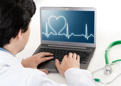 doctor working on laptop with heart rhythm ekg on screen - stock photo