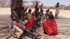 Samburu tribesmen resting against a tree. Stock Footage
