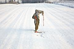 sad, ragged  and freezing scarecrow in winter on the snowfield - stock photo