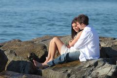 Couple flirting and hugging beside the sea Stock Photos