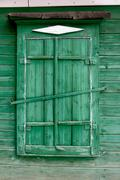 Old wooden window in a wall painte in green color Stock Photos