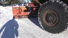 Winter snow cleaning machine is sprinkling salt, sand on a road - stock footage
