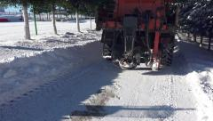 Winter snow cleaning machine is sprinkling salt, sand on a road Stock Footage